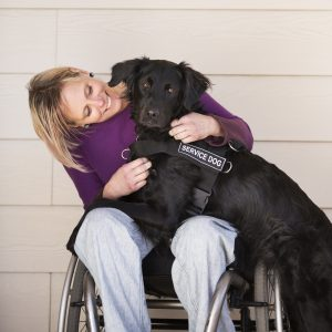 Photo Of The Happy Woman On The Disabled Carriage With A Service Dog