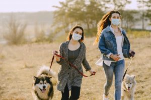 women wearing face masks while running with their dogs