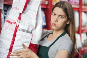 Portrait of mid adult saleswoman carrying heavy food package in pet store